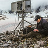 "Joel Bailey, a research professional with UAF's Institute of Northern Engineering, downloads data from a weather station above the surface of the Jarvis Glacier in the eastern Alaska Range.  <div class=""ss-paypal-button"">Filename: AAR-14-4256-306.jpg</div><div class=""ss-paypal-button-end""></div>"