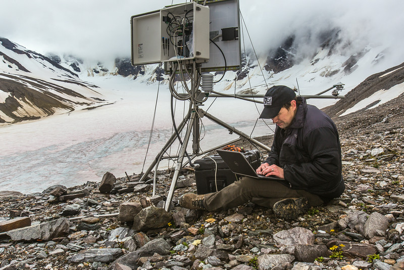 """Joel Bailey, a research professional with UAF's Institute of Northern Engineering, downloads data from a weather station above the surface of the Jarvis Glacier in the eastern Alaska Range.  <div class=""""ss-paypal-button"""">Filename: AAR-14-4256-306.jpg</div><div class=""""ss-paypal-button-end""""></div>"""