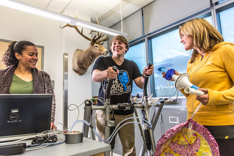 """Chris Wilson gets ready to exercise on a stair step machine while Ashley Jacobs (in yellow) and Marisol Bastiani stand by to collect data during a human physiology lab in the Murie Building.  <div class=""""ss-paypal-button"""">Filename: AAR-13-3983-4.jpg</div><div class=""""ss-paypal-button-end"""" style=""""""""></div>"""