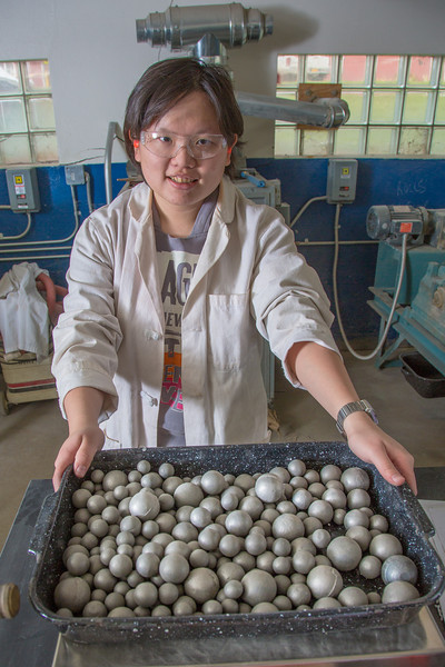 "Hsin-Hui Yen stands by a tray of steel ball bearings used to crush ore as part of her research at the Mineral Industry Research Lab (MIRL) facility in the barn at the UAF Agricultural and Forestry Experiment Station.  <div class=""ss-paypal-button"">Filename: AAR-12-3549-045.jpg</div><div class=""ss-paypal-button-end"" style=""""></div>"