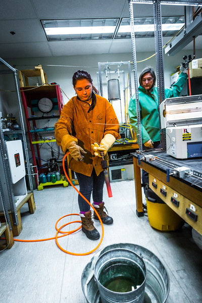 """Research Assistant Professor Jessica Larsen, at right, operates the valve while volcanology graduate student Rebecca deGraffenreid uses water to cool down a rod which contains volcanic remnants after it was pulled from a furnace in the Reichardt Building petrology lab.  <div class=""""ss-paypal-button"""">Filename: AAR-16-4828-088.jpg</div><div class=""""ss-paypal-button-end""""></div>"""
