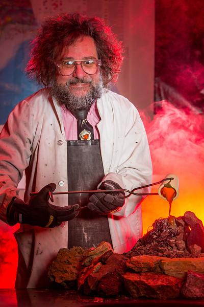 """Geology professor Rainer Newberry pours hot lava over volcanic basalt during a set-up photoshoot in a Reichardt Building lab in on the Fairbanks campus.  <div class=""""ss-paypal-button"""">Filename: AAR-13-3732-34.jpg</div><div class=""""ss-paypal-button-end"""" style=""""""""></div>"""