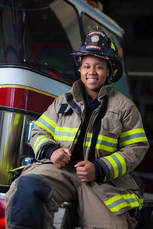 UAF student firefighter/EMTs Lillian Hampton poses by one of the firetrucks housed in the Whitaker Building on the Fairbanks campus.  Filename: AAR-11-3223-158.jpg
