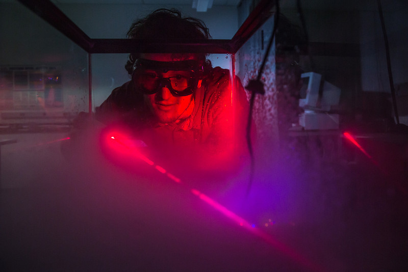 """Physics major Michael Succone experiments with light from a laser as its being scattered by clouds of condensation inside an aquarium in a Reichardt Building lab.  <div class=""""ss-paypal-button"""">Filename: AAR-13-4009-27.jpg</div><div class=""""ss-paypal-button-end"""" style=""""""""></div>"""