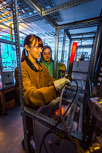 Ph.D. candidate Amanda Lindoo pulls a rod containing volcanic remnants from a furnace in the Reichardt Building petrology lab under the watchful gaze of Research Assistant Professor Jessica Larsen.
