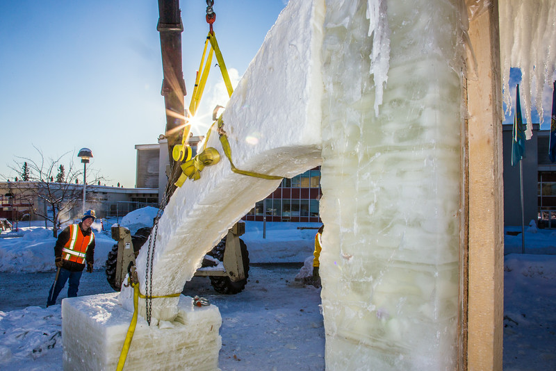 """Volunteers from GHEMM, Inc. use a crane to lift the buttresses for this year's student-built ice arch into position in Cornerstone Plaza on campus. The annual ice arch is designed and built by a team of engineering students, a UAF tradition going back more than 60 years.  <div class=""""ss-paypal-button"""">Filename: AAR-14-4078-21.jpg</div><div class=""""ss-paypal-button-end""""></div>"""