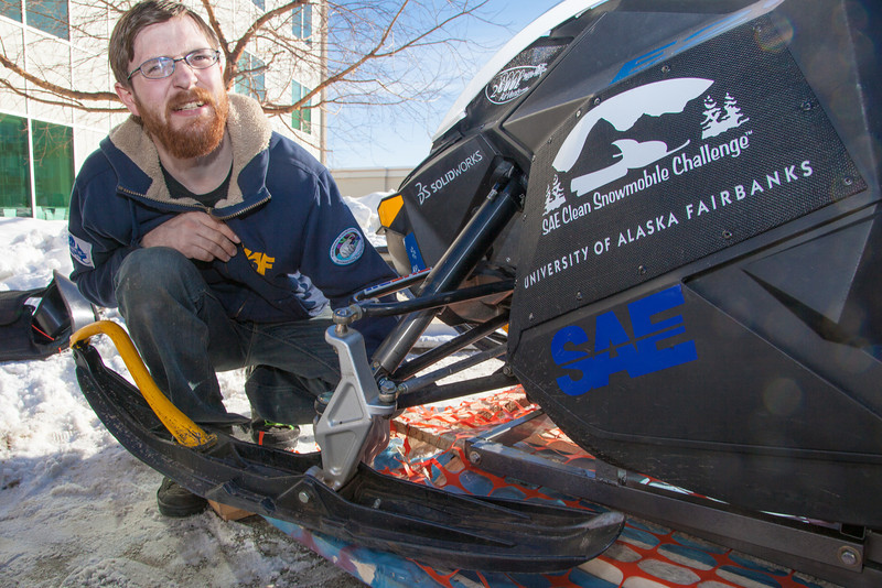 """Mechanical engineering major Isaac Thompson unpacks the snowmobile in front of the Duckering Building after its return from competing in the Society of Automotive Engineers' Clean Snowmobile Challenge in Houghton, Mich.  <div class=""""ss-paypal-button"""">Filename: AAR-12-3337-07.jpg</div><div class=""""ss-paypal-button-end"""" style=""""""""></div>"""