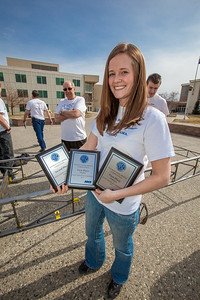 Co-captain Amanda Green with UAF's 2012 steel bridge team displays a couple first-place and a second-place plaque won by the team in the regional competiton.  Filename: AAR-12-3388-33.jpg