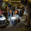 "Art major Joel Isaak, center, fills a mold with molten bronze as part of the process of creating a life-sized sculpture for his senior thesis in the UAF Fine Arts complex.  <div class=""ss-paypal-button"">Filename: AAR-12-3347-094.jpg</div><div class=""ss-paypal-button-end"" style=""""></div>"