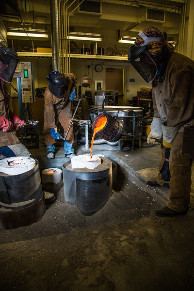 """Art major Joel Isaak, center, fills a mold with molten bronze as part of the process of creating a life-sized sculpture for his senior thesis in the UAF Fine Arts complex.  <div class=""""ss-paypal-button"""">Filename: AAR-12-3347-094.jpg</div><div class=""""ss-paypal-button-end"""" style=""""""""></div>"""
