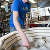 "Art major Ian Wilkinson removes some of the 1,000-plus same-sized bowls he made for his senior thesis from a kiln in the UAF ceramics studio.  <div class=""ss-paypal-button"">Filename: AAR-13-3744-14.jpg</div><div class=""ss-paypal-button-end"" style=""""></div>"
