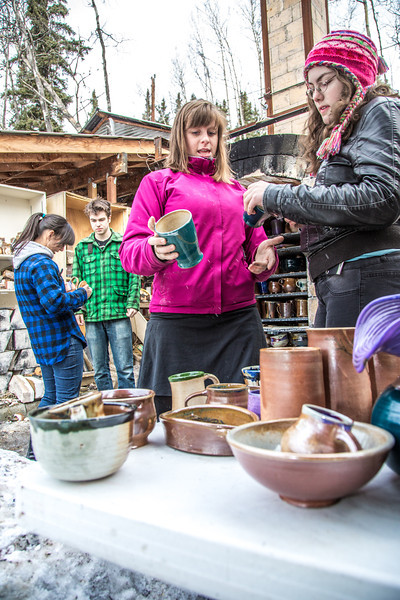 """UAF ceramic students inspect their projects after unloading them from an outdoor kiln fired with recycled vegetable oil.  <div class=""""ss-paypal-button"""">Filename: AAR-13-3814-37.jpg</div><div class=""""ss-paypal-button-end"""" style=""""""""></div>"""