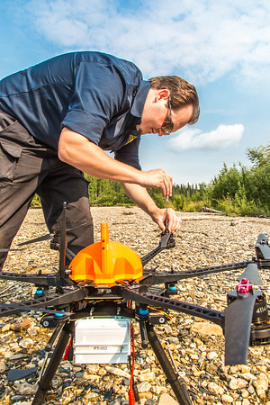 "Trevor Parcell with the Alaska Center for Unmanned Aircraft Systems Integration (ACUASI) sets up a piloting station on a gravel bar along the upper Chena River. The UAV pilot was taking part in a joint effort with the U.S. Fish and Wildlife Service to collect video of important king salmon spawning habitat.  <div class=""ss-paypal-button"">Filename: AAR-15-4593-103.jpg</div><div class=""ss-paypal-button-end""></div>"