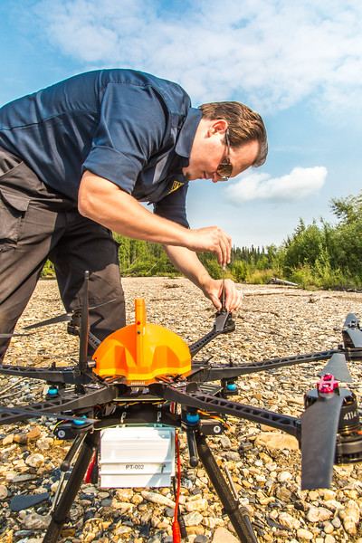 """Trevor Parcell with the Alaska Center for Unmanned Aircraft Systems Integration (ACUASI) sets up a piloting station on a gravel bar along the upper Chena River. The UAV pilot was taking part in a joint effort with the U.S. Fish and Wildlife Service to collect video of important king salmon spawning habitat.  <div class=""""ss-paypal-button"""">Filename: AAR-15-4593-103.jpg</div><div class=""""ss-paypal-button-end""""></div>"""