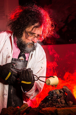 Geology professor Rainer Newberry pours hot lava over volcanic basalt during a set-up photoshoot in a Reichardt Building lab in on the Fairbanks campus.  Filename: AAR-13-3732-30.jpg