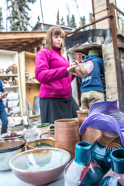 """UAF ceramic students unload their projects from an outdoor kiln fired with recycled vegetable oil.  <div class=""""ss-paypal-button"""">Filename: AAR-13-3814-26.jpg</div><div class=""""ss-paypal-button-end"""" style=""""""""></div>"""