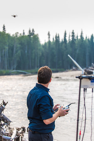 Trevor Parcell, a pilot with UAF's Alaska Center for Unmanned Aerial Systems Integration (ACUASI) flies a drone over the upper Chena River July 31. Parcell and other ACUASI technicians were working with the U.S. Fish and Wildlife Service to obtain quality video footage of the prime king salmon habitat along that stretch of the popular river.  Filename: AAR-15-4593-258.jpg