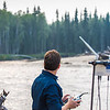 "Trevor Parcell, a pilot with UAF's Alaska Center for Unmanned Aerial Systems Integration (ACUASI) flies a drone over the upper Chena River July 31. Parcell and other ACUASI technicians were working with the U.S. Fish and Wildlife Service to obtain quality video footage of the prime king salmon habitat along that stretch of the popular river.  <div class=""ss-paypal-button"">Filename: AAR-15-4593-258.jpg</div><div class=""ss-paypal-button-end""></div>"
