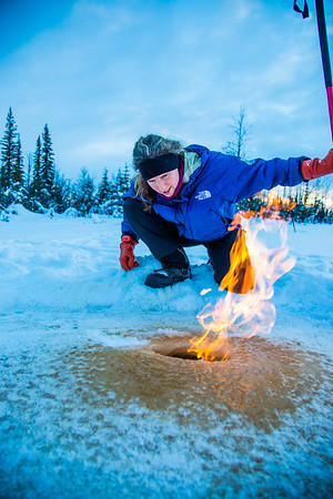 Research Associate Professor Katey Walter Anthony inspects flaming methane gas seeping from a hole in the ice on the surface of a pond on the UAF campus. The naturally occurring phenomenon is made worse by thawing permafrost and increased plant decay caused by global warming.  Filename: AAR-16-4815-26.jpg