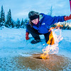 "Research Associate Professor Katey Walter Anthony inspects flaming methane gas seeping from a hole in the ice on the surface of a pond on the UAF campus. The naturally occurring phenomenon is made worse by thawing permafrost and increased plant decay caused by global warming.  <div class=""ss-paypal-button"">Filename: AAR-16-4815-26.jpg</div><div class=""ss-paypal-button-end""></div>"