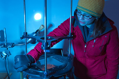 "Sophomore Tiffany Green inspects crystal formations in a thin slice of ice in the Elvey Building ""Cold Room"" during a lab exercise in her Ice in Climate Systems class.  Filename: AAR-12-3330-097.jpg"