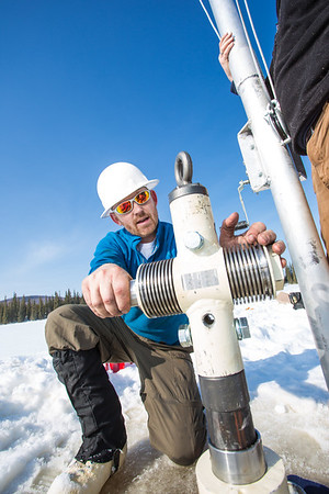 Associate Professor Mat Wooller tests a new vibra-coring system through a hole in lake ice to sample long cores of sediment deep below the lake's bottom.  Filename: AAR-12-3346-031.jpg