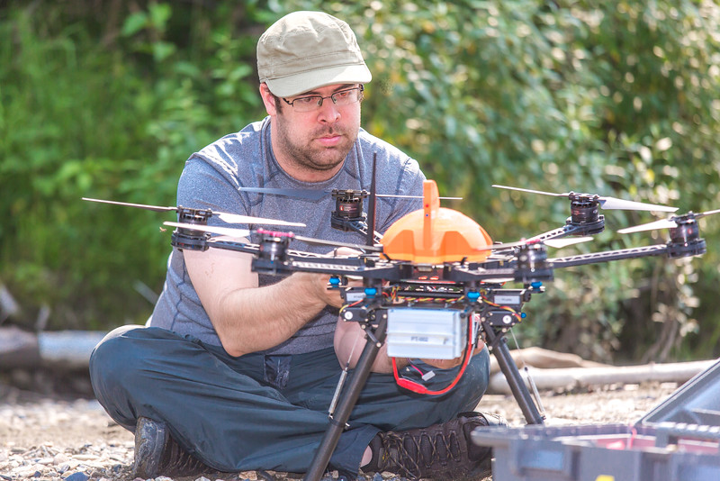 """Carl France with the Alaska Center for Unmanned Aircraft Systems Integration (ACUASI) sets up a piloting station on a gravel bar along the upper Chena River. The UAV pilot was taking part in a joint effort with the U.S. Fish and Wildlife Service to collect video of important king salmon spawning habitat.  <div class=""""ss-paypal-button"""">Filename: AAR-15-4593-118.jpg</div><div class=""""ss-paypal-button-end""""></div>"""