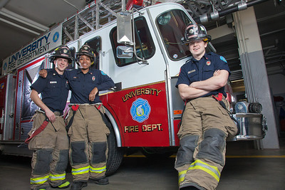 UAF student firefighters/EMTs John McGee, left, Lillian Hampton and Ethan Stevenson pose by one of the firetrucks housed in the Whitaker Building on the Fairbanks campus.  Filename: AAR-11-3223-108.jpg