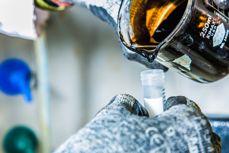 """Graduate student Mukul Chavan pours a sample of heavy crude oil from the Kaparuk field on Alaska's North Slope. Chavan and other students in UAF's petroleum engineering program are using the samples to experiment with ways to recover more oil from existing fields.  <div class=""""ss-paypal-button"""">Filename: AAR-13-3918-124.jpg</div><div class=""""ss-paypal-button-end"""" style=""""""""></div>"""