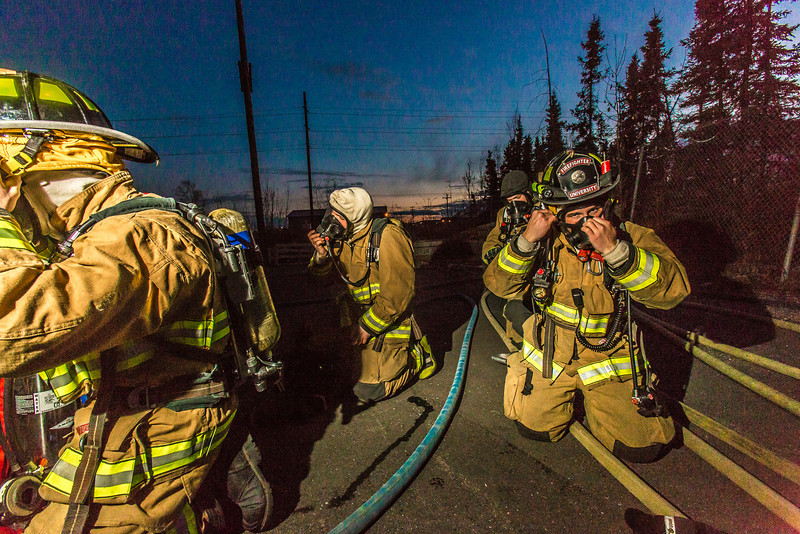 """Student fire fighter Crosby Hanson, right, dons his mask along with other members of the University Fire Department before entering a burning building as part of a live training drill at the Fairbanks Fire Training Center.  <div class=""""ss-paypal-button"""">Filename: AAR-13-3978-35.jpg</div><div class=""""ss-paypal-button-end"""" style=""""""""></div>"""