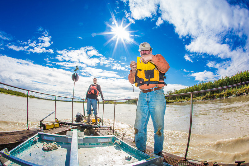 "Jack Schmid, front, and Paul Duvoy, research professionals with the Alaska Center for Energy and Power, record measurements on a prototype deployment boom on the Tanana River near Nenana. The pair are part of a team conducting research on the feasibility of using the river current to generate electricity for potential use throughout rural Alaska.  <div class=""ss-paypal-button"">Filename: AAR-12-3500-068.jpg</div><div class=""ss-paypal-button-end"" style=""""></div>"