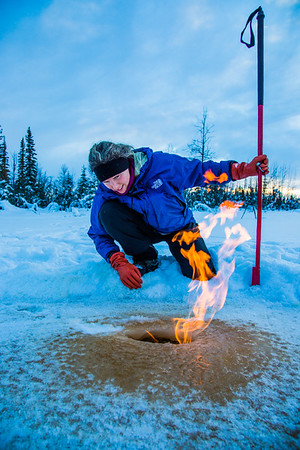 Research Associate Professor Katey Walter Anthony inspects flaming methane gas seeping from a hole in the ice on the surface of a pond on the UAF campus. The naturally occurring phenomenon is made worse by thawing permafrost and increased plant decay caused by global warming.  Filename: AAR-16-4815-32.jpg