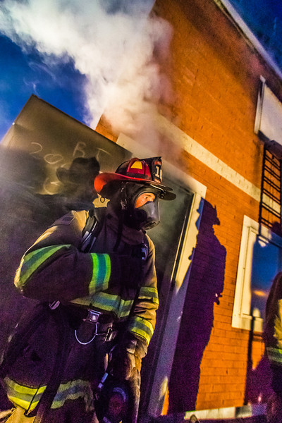 """UFD Captain Ben Fleagle exits a burning building during a live training drill at the Fairbanks Fire Training Center in South Fairbanks. McClean was helping lead the session with about 30 students participating  department's Tuesday night drill Oct. 22.  <div class=""""ss-paypal-button"""">Filename: AAR-13-3978-140.jpg</div><div class=""""ss-paypal-button-end"""" style=""""""""></div>"""
