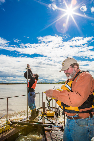 "Jack Schmid, front, and Paul Duvoy, research professionals with the Alaska Center for Energy and Power, record measurements on a prototype deployment boom on the Tanana River near Nenana. The pair are part of a team conducting research on the feasibility of using the river current to generate electricity for potential use throughout rural Alaska.  <div class=""ss-paypal-button"">Filename: AAR-12-3500-047.jpg</div><div class=""ss-paypal-button-end"" style=""""></div>"