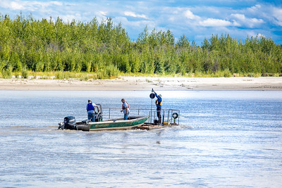 Researchers with UAF's School of Fisheries and Ocean Sciences and the Alaska Center for Energy and Power (ACEP) check equipment on a prototype deployment boom on a barge anchored in the Tanana River near Nenana. They're part of a team conducting research on the feasibility of using the river current  to generate electricity for potential use throughout rural Alaska.  Filename: AAR-12-3500-219.jpg