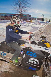 Engineering major Isaac Thompson drives the electric snowmachine he and other members of his team helped modify into the Duckering Building after its return to campus after claiming the top prize in the SAE Clean Showmobile Challenge in Houghton, Mich.  Filename: AAR-12-3337-54.jpg