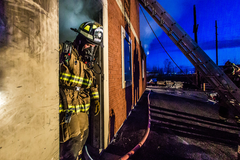 """Student fire-fighting engineer Spencer McClean exits a burning building during a live training drill at the Fairbanks Fire Training Center in South Fairbanks. McClean was one of about 30 students participating  in the University Fire Department's Tuesday night drill Oct. 22.  <div class=""""ss-paypal-button"""">Filename: AAR-13-3978-134.jpg</div><div class=""""ss-paypal-button-end"""" style=""""""""></div>"""