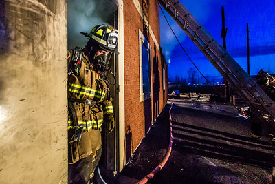 Student fire-fighting engineer Spencer McClean exits a burning building during a live training drill at the Fairbanks Fire Training Center in South Fairbanks. McClean was one of about 30 students participating  in the University Fire Department's Tuesday night drill Oct. 22.  Filename: AAR-13-3978-134.jpg