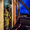 "Student fire-fighting engineer Spencer McClean exits a burning building during a live training drill at the Fairbanks Fire Training Center in South Fairbanks. McClean was one of about 30 students participating  in the University Fire Department's Tuesday night drill Oct. 22.  <div class=""ss-paypal-button"">Filename: AAR-13-3978-134.jpg</div><div class=""ss-paypal-button-end"" style=""""></div>"
