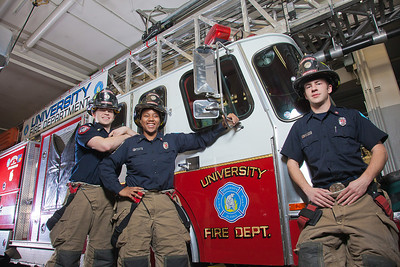 UAF student firefighters/EMTs John McGee, left, Lillian Hampton and Ethan Stevenson pose by one of the firetrucks housed in the Whitaker Building on the Fairbanks campus.  Filename: AAR-11-3223-98.jpg