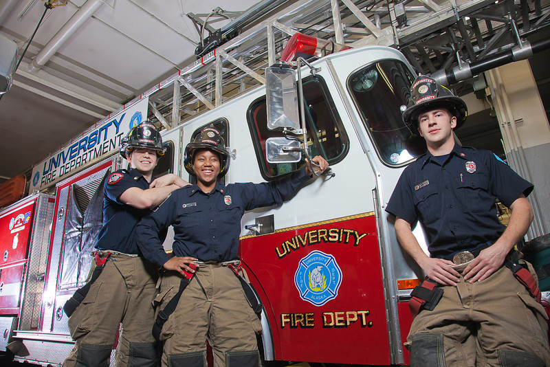 """UAF student firefighters/EMTs John McGee, left, Lillian Hampton and Ethan Stevenson pose by one of the firetrucks housed in the Whitaker Building on the Fairbanks campus.  <div class=""""ss-paypal-button"""">Filename: AAR-11-3223-98.jpg</div><div class=""""ss-paypal-button-end"""" style=""""""""></div>"""
