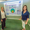 "Psychology major Brittani King, rights, stands with Professor Ellen Lopez in front of her poster during UAF's Research Day Poster Session in Wood Center.  <div class=""ss-paypal-button"">Filename: AAR-14-4169-4.jpg</div><div class=""ss-paypal-button-end""></div>"