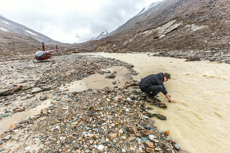 """Matvey Debolskiy, a Ph.D. student in geophysics, collects water samples from the headwaters of the Jarvis River, high in the eastern Alaska Range.  <div class=""""ss-paypal-button"""">Filename: AAR-14-4256-377.jpg</div><div class=""""ss-paypal-button-end""""></div>"""