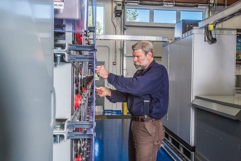 """Research technician David Light works with the battery bank in one of the modules in the Alaska Center for Energy and Power Technology Center.  <div class=""""ss-paypal-button"""">Filename: AAR-12-3479-043.jpg</div><div class=""""ss-paypal-button-end"""" style=""""""""></div>"""