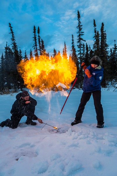 """Research Associate Professor Katey Walter Anthony and a research assistant set fire to escaping methane gas trapped beneath the ice on a pond on the UAF campus. The naturally occurring phenomenon is made worse by thawing permafrost and increased plant decay caused by global warming.  <div class=""""ss-paypal-button"""">Filename: AAR-16-4815-03.jpg</div><div class=""""ss-paypal-button-end""""></div>"""