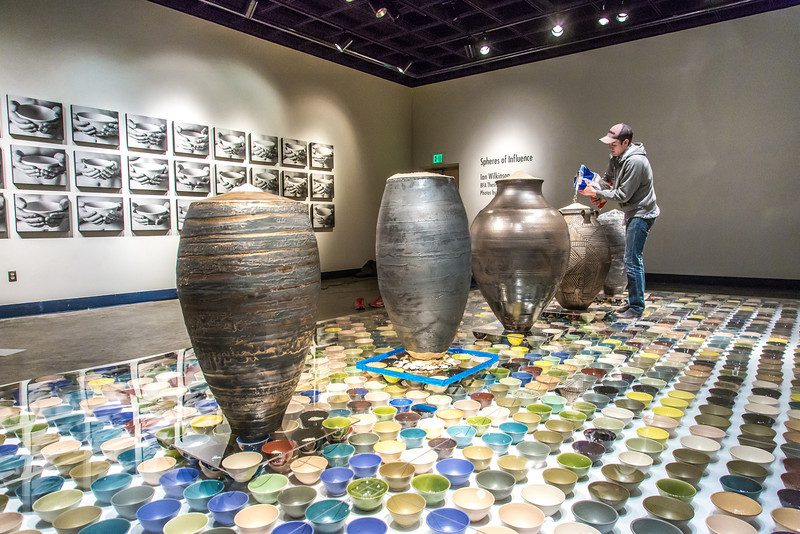 """Art major Ian Wilkinson pours uncooked rice into the top of one of his ceramic pieces in the UAF Fine Arts gallery. His BFA thesis project, Spheres of Influence, raised more than $18,000 for the Fairbanks Food Bank through the sale of his 1,200 bowls.  <div class=""""ss-paypal-button"""">Filename: AAR-13-3775-22.jpg</div><div class=""""ss-paypal-button-end"""" style=""""""""></div>"""