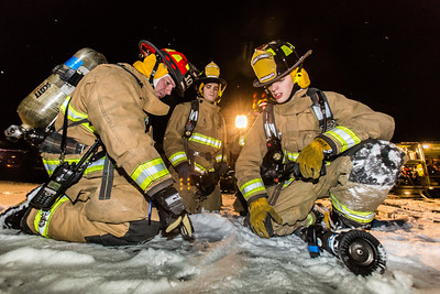 UFD Captain Forrest Kuiper, left, gives instructions to student firefighters during a live drill at the Fairbanks International Airport.  Filename: AAR-13-3995-36.jpg