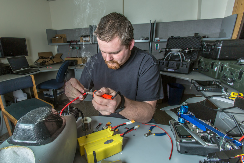 "Technician Michael Cook works on one of the unmanned aerial vehicles in UAF's Alaska Center for Unmanned Aircraft Systems Integration (ACUASI) shop in south Fairbanks.  <div class=""ss-paypal-button"">Filename: AAR-13-4026-24.jpg</div><div class=""ss-paypal-button-end""></div>"
