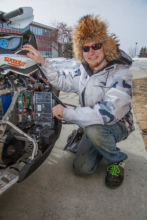 Mechanical enineering major Isaac Thompson makes some adjustments to the UAF team's snowmobile in front of the Duckering Building after its return from competing in the Society of Automotive Engineers' Clean Snowmobile Challenge in Houghton, Mich.  Filename: AAR-12-3345-015.jpg