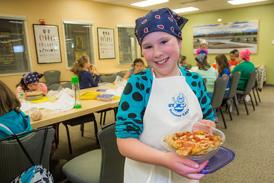 Ten-year-old Melody Lackey displays the pepperoni pizza she made during the UAF Summer Sessions Baking Blitz May 28 in the Hutchison kitchen.  Filename: AAR-14-4203-68.jpg
